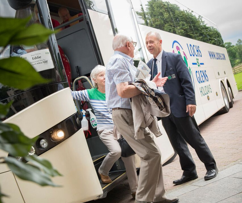 Luxury Coach Tour driver helping guests out of the coach on a holiday to Scotland